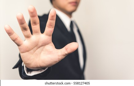 Businessman showing stop sign with hand