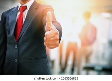 Businessman showing thumbs up in office work place