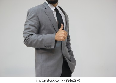 Businessman showing thumbs up on gray background