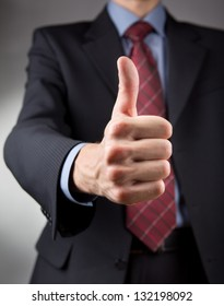 Businessman showing thumbs up sign. Neutral background