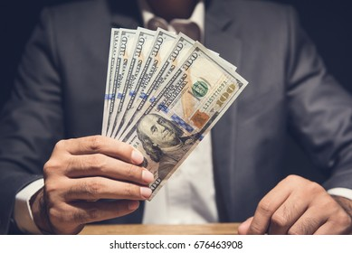 Businessman showing US dollar bills at the table in dark background - making money, bribery and venality concepts