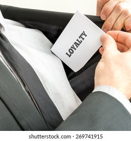 Businessman showing a white card reading - Loyalty - as he withdraws it from the pocket of his suit jacket.