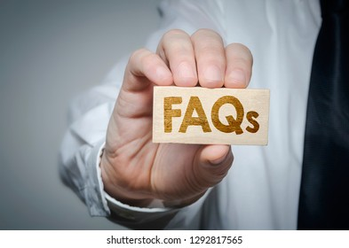 Businessman showing wooden block displaying FAQ word. Questions and answers concept.