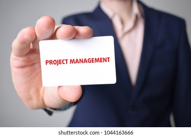 Businessman shows business card with the inscription:PROJECT MANAGEMENT