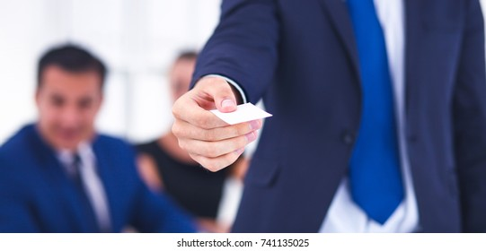 Businessman shows business card standing in office