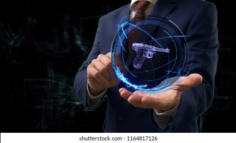 Businessman shows concept hologram 3d gun on his hand. Man in business suit with future technology screen and modern cosmic background