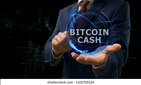 Businessman shows concept hologram Bitcoin cash on his hand. Man in business suit with future technology screen and modern cosmic background