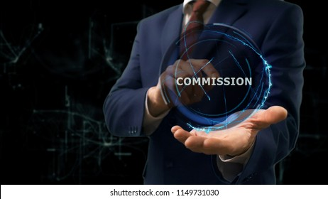 Businessman shows concept hologram Commission on his hand. Man in business suit with future technology screen and modern cosmic background
