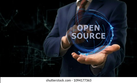 Businessman shows concept hologram Open source on his hand. Man in business suit with future technology screen and modern cosmic background
