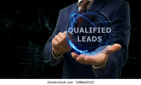 Businessman shows concept hologram Qualified leads on his hand. Man in business suit with future technology screen and modern cosmic background