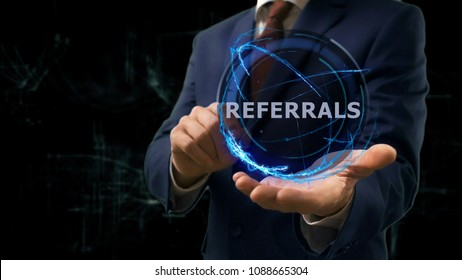 Businessman shows concept hologram Referrals on his hand. Man in business suit with future technology screen and modern cosmic background