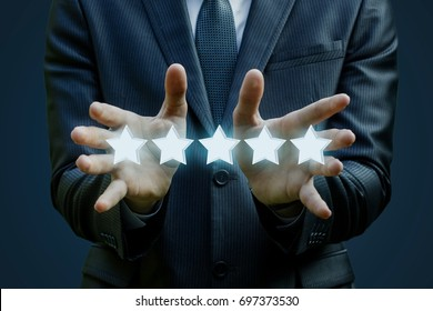 Businessman shows a five stars rating on blue background
