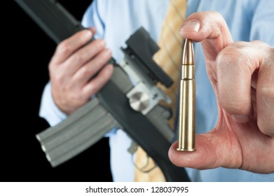 A businessman shows a large 223 bullet for his automatic assault rifle.