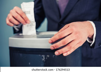 A Businessman is shredding important documents