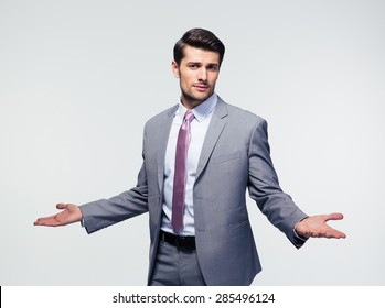 Businessman shrugging shoulders over gray background. Looking at camera