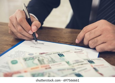 Businessman signing agreement contract paper with money, Russian ruble banknotes, on the table - loan and financial concept