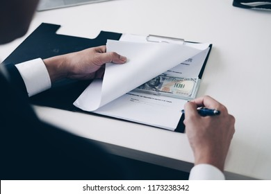 Businessman signing contract with hides money while making deal to agreement a contract, Bribe in the form of dollar bills, Bribery and corruption concept,