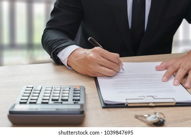 Businessman signing contract with key and calculator on wooden desk.