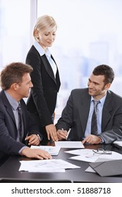 Businessman signing contract at meeting, smiling assistant pointing at document.