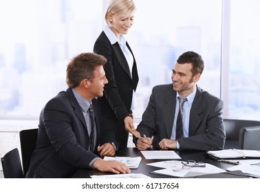 Businessman signing contract at meeting, smiling assistant pointing at document.?