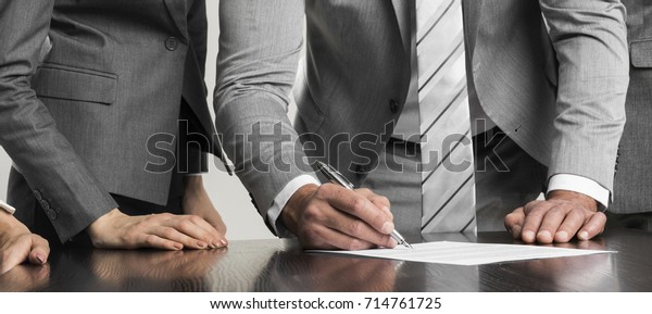 Businessman signing contract while his team is looking at him