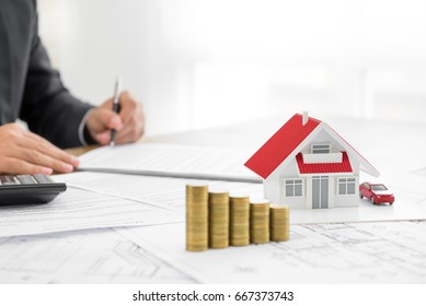 Businessman signing document with money and house model on the table - real estate, properties and investment concepts