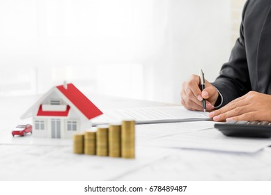 Businessman signing document with money and house model on the table - real estate and properties financial concepts