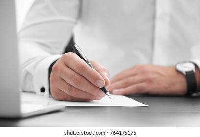Businessman signing document in office
