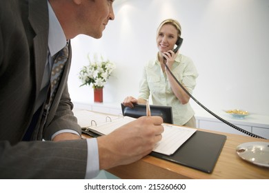 Businessman signing guestbook in reception area, female receptionist using telephone, smiling