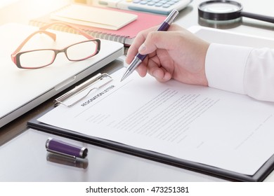 Businessman signing his resignation letter on his desk before sending to his boss to resign his job.