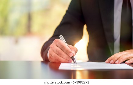 Businessman Is Signing A Legal Document In Office