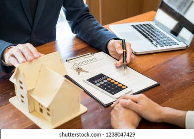 Businessman signs contract behind home architectural modelDiscussion with a real estate agent rental company staffat the office property appraisal and valuation concept