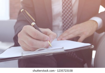 Businessman signs a contract. Holding pen in hand.