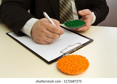Businessman signs a contract for the supply of plastic granules for industry. Plastic raw material in granules. Polymer, plastic resin.