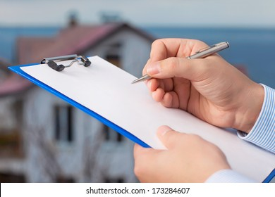businessman signs a document on the background of an apartment building with blue sky