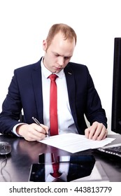 Businessman signs documents in the workplace.