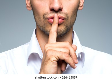 Businessman silent quiet gesture with finger