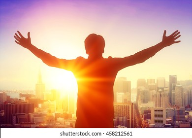 Businessman silhouette celebrating success on city background with sunlight