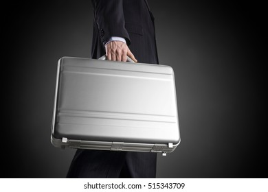 Businessman with a silver suitcase on a dark background with circle gradient