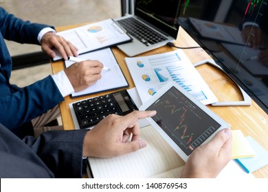businessman sit at ther table looking at computer laptop in the office , they talking about stock market invest or talk with customer