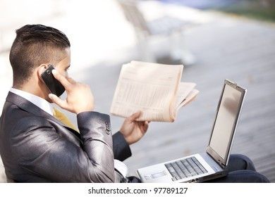 Businessman sited in a bench working with his laptop, calling at the cellular and reading his newspaper