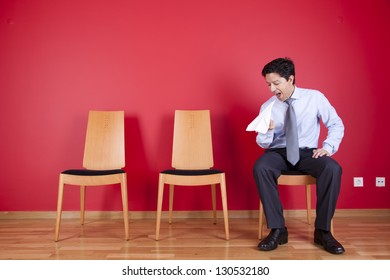businessman sited next to a red wall trowing paper planes