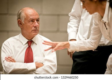 Businessman sits with crossed arms as he listens to the argument of a businesswoman who gestures as she speaks emphatically.