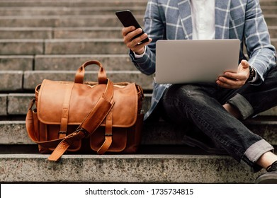 businessman sits on a shoe with laptop and brown leather bag