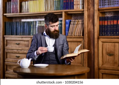Businessman sits in vintage interior, holds book and cup of tea. Bearded man in luxury suit in his cabinet. Mature man with calm face enjoys reading. Luxury lifestyle, vintage fashion, tea concept.