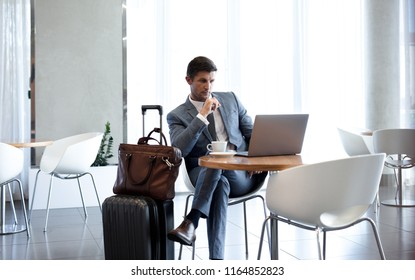 Businessman sitting in airport business lounge and looking at laptop on table. Business man sitting at airport lounge with laptop.