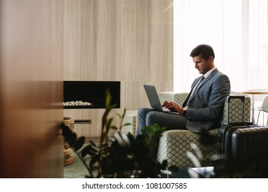 Businessman sitting at airport waiting lounge and working on laptop computer. Male executive in airport business lounge waiting for flight.