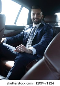 businessman sitting in the back seat of a car