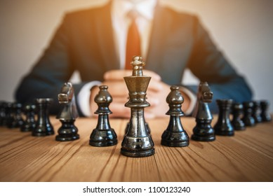 businessman sitting behind chess figure in competition success play. strategy, management or leadership concept