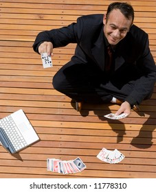 A businessman sitting behind a laptop and pile of cards holding up a 9 of spades.